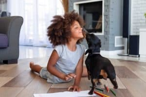 Dog licking young girl while she colors